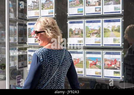 Woman looking in an estate agent's window at properties for sale. England UK - Stock Photo