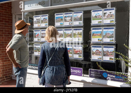 Couple looking in an estate agent's window at properties for sale. England UK - Stock Photo