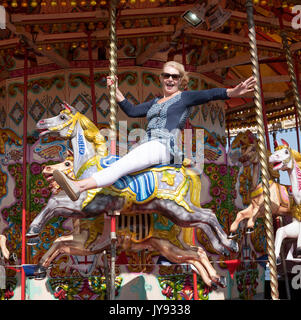Woman riding a Carousel horse at the seaside - Stock Photo