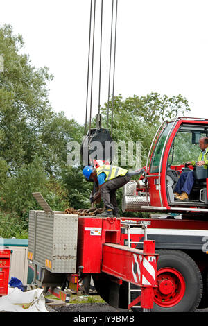 Man working crane lifting chains at Enslow Marina alongside the South Oxford Canal - Stock Photo