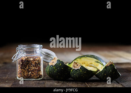 Tasty pumpkin and spices on a wooden kitchen table, black background - Stock Photo