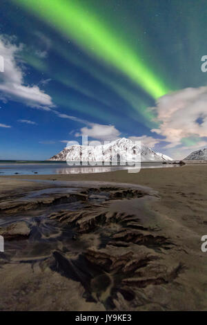 Northern Lights illuminate Skagsanden beach and the snowy peaks. Lofoten Islands Northern Norway Europe - Stock Photo
