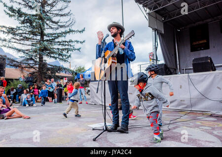 Langhorne Slim performs while kids play around him at Canmore Folk Music Festival, Canmore, Alberta, Canada - Stock Photo