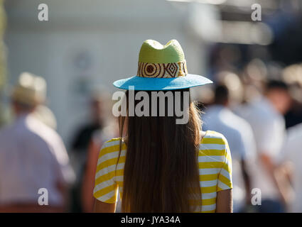 Woman wearing hat and sitting outside of tennis court at Wimbledon Championships 2017, London, Great Britain, United - Stock Photo