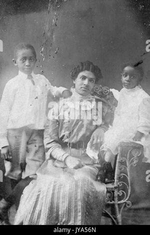 African-American mother in formal dress posing for a studio portrait, sitting in a chair, her two children standing - Stock Photo