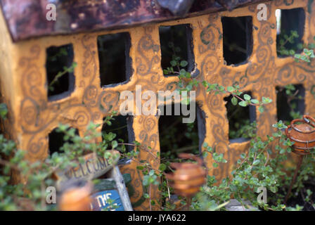 Yellow ceramic fairy house in a leafy garden Stock Photo
