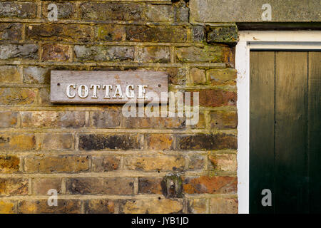 Cottage wooden sign on a brick wall. Landscape format. - Stock Photo