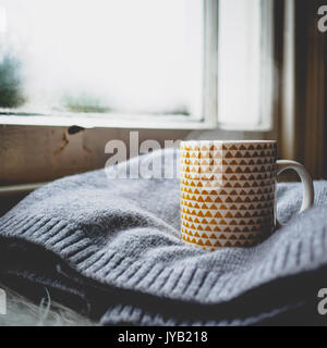 Mug decorated with yellow geometrical elements on a wool sweater in front of a sash window. Squared format. - Stock Photo