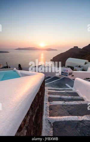 Sunset over the Aegean Sea seen from an alley of stairs of the old village of Firostefani Santorini Cyclades Greece - Stock Photo