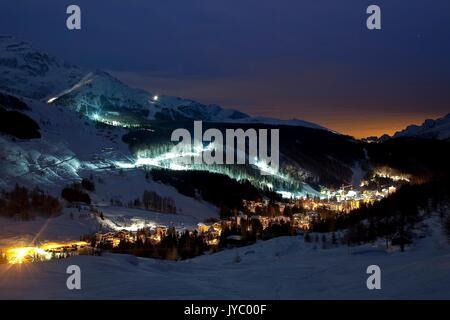 Madesimo and its ski slopes lit during a full moon night. Valchiavenna. Vallespluga. Valtellina. Lombardy. Italy. - Stock Photo