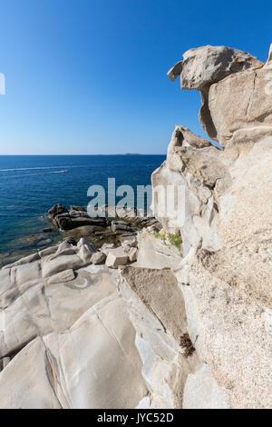 The sun shines on the white rocks eroded by wind framing the blue sea Punta Molentis Villasimius Cagliari Sardinia - Stock Photo