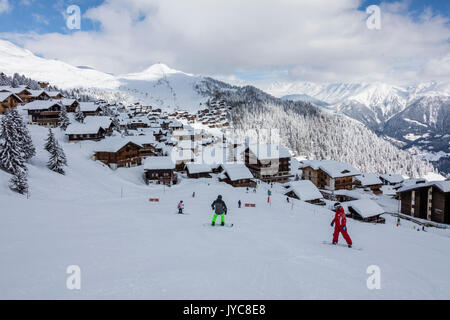 Snowboarders on ski slopes frames the typical alpine village Stock ...