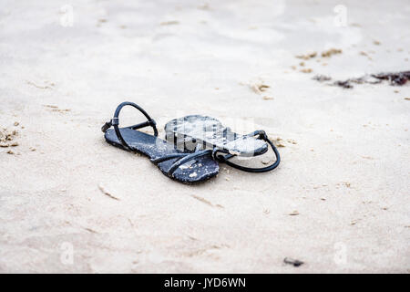 black shoes in the white beach sand - Stock Photo