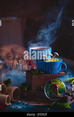 Ceramic cups of tea with mushrooms in a wizard workplace. Magic still life with smoke, scrolls, bird skulls and - Stock Photo