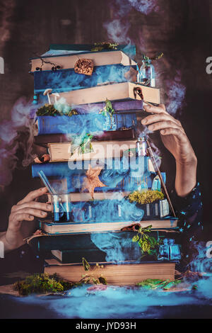 A pile of magical books with wizard hands. - Stock Photo