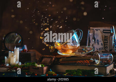 Tea splash in a glass cup on a wooden background with candles, mystery newspaper clips, books, leaves and moss. - Stock Photo