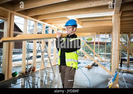 Mature Carpenter Carrying Wood At Construction Site - Stock Photo