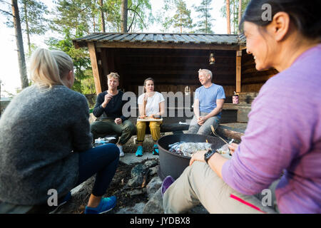 Friends Talking While Having Food By Firepit In Forest - Stock Photo