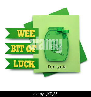 Creative St. Patricks Day concept photo of a bottle with shamrocks made of paper on white background. - Stock Photo