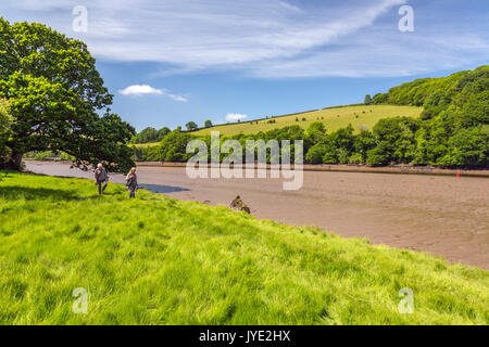 Two ladies walking along a quiet wooded stretch of the River Dart at low tide near Sharpham, Devon, England, UK - Stock Photo