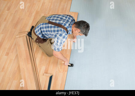 High Angle View Of A Worker Assembling New Laminate Floor - Stock Photo