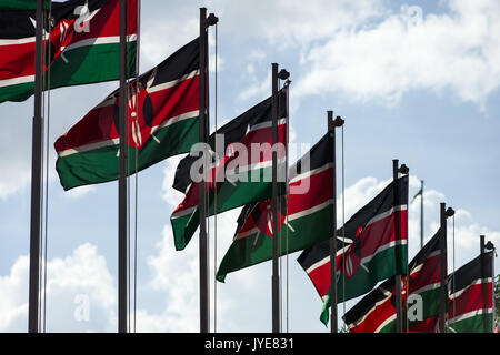 A row of Kenyan flags on poles waving in the wind on a sunny day, Nairobi, Kenya - Stock Photo