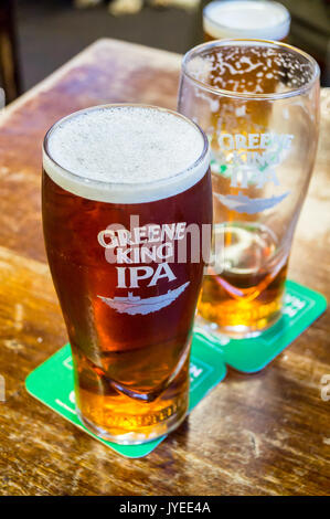 Pint glasses of Greene King IPA real ale on a bar at the Crown Inn, Leiston, Suffolk, England - Stock Photo
