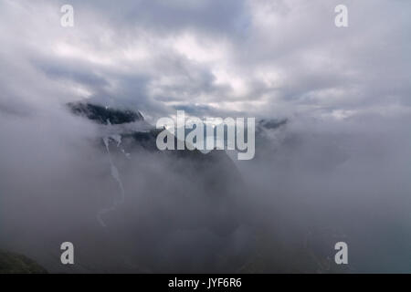 Top view of sea framed by silhouettes of peaks covered by clouds and mist Reinebringen Moskenes Lofoten Islands - Stock Photo