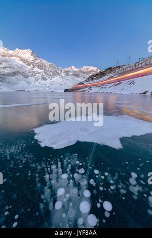 The Bernina Express train runs beside the frozen Lago Bianco Bernina Pass canton of Graubünden Engadine Switzerland - Stock Photo