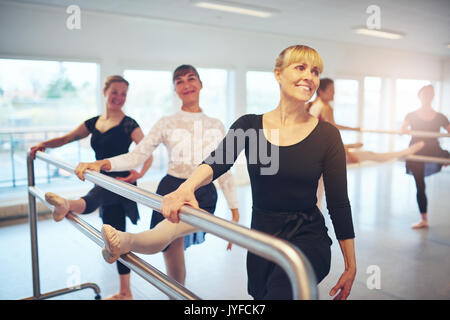 Group of adult ballerinas exercising and doing gymnastics at handrail in the ballet class. - Stock Photo