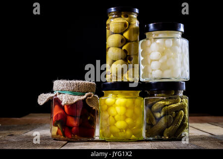 Mortar, vegetables in jars for the winter, wooden table in the old kitchen. Black background. - Stock Photo