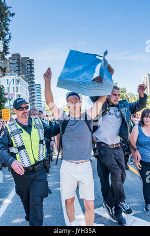 Vancouver, Canada. 19th Aug, 2017. Angry man rips anti refugee sign from counter protester at Anti-Racism rally, - Stock Photo