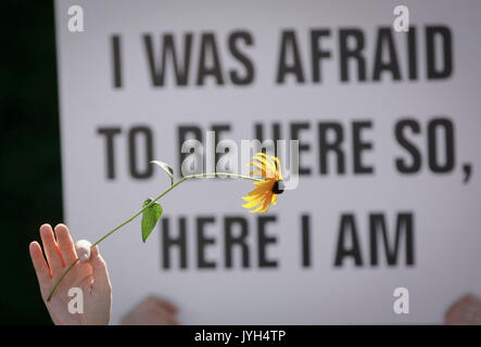 Vancouver, Canada. 19th Aug, 2017. A protestor holds up a flower in front of a sign during an anti-racism rally - Stock Photo