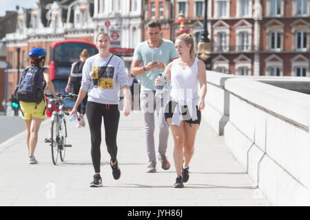 London, UK. 20th Aug, 2017. UK Weather. Pedestrians and joggers enjoy the sunshine on Putney Bridge London on a - Stock Photo