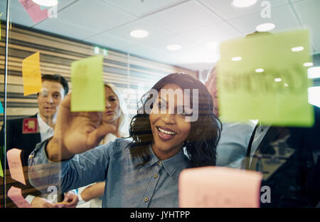 Smiling businesswoman putting sticky note on glass, group of colleagues behind her - Stock Photo