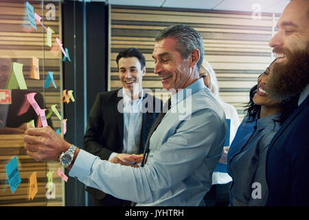 Side view of smiling businesspeople touching and looking at sticky notes on glass in office - Stock Photo