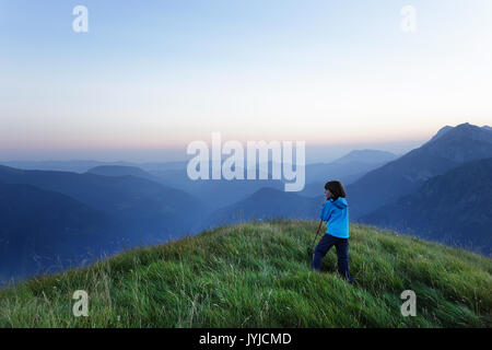 Young boy having a rest and leaning on a walking stick and looking at panoramic view on twilight, Slatnik, SLovenia. - Stock Photo