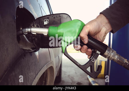 Fill up fuel at petrol station. Filling a dirty car at a gas station. Fuelling nozzle for refuelling a car in man's - Stock Photo
