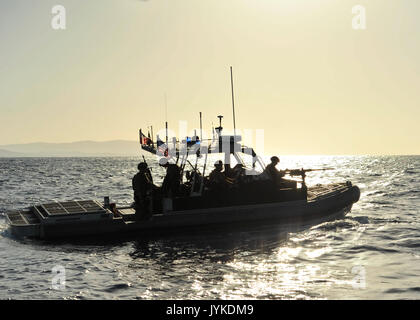 Coast Guardsmen from Port Security Unit 305 aboard a 32-foot Transportable Port Security Boat enforce a security - Stock Photo