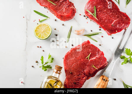 Fresh raw meat. Beef tenderloin, steaks, on a white marble table. With olive oil, spices for cooking - basil, rosemary, - Stock Photo