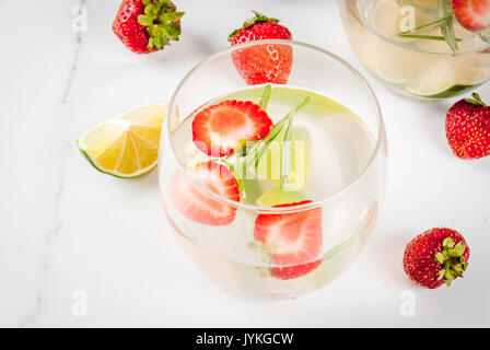 Summer refreshing cocktail. Lemonade with lime, fresh strawberries and rosemary. On a white marble table. Copy space - Stock Photo