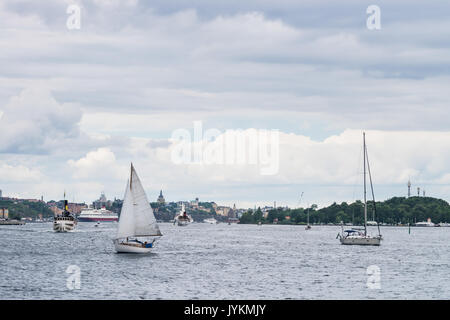 View over boats sailing in Baltic sea in Stockholm, Sweden, with the city in the background - Stock Photo