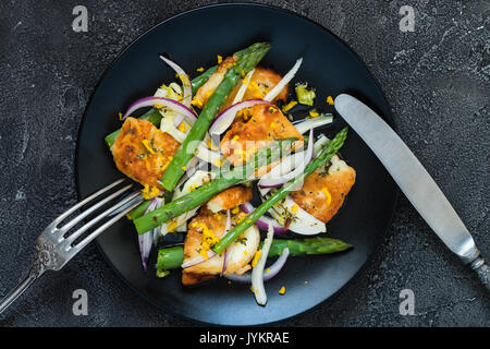 Salad with fried halloumi, asparagus and orange zest. Top view with cutlery. Dark concrete background - Stock Photo
