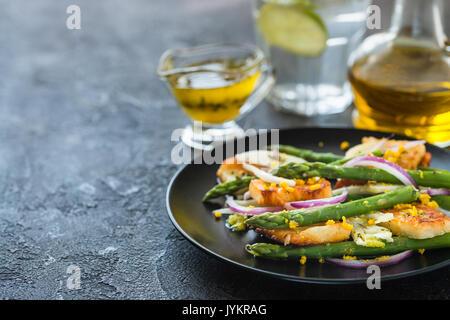 Salad with fried halloumi, asparagus and orange zest. Copy space. Dark concrete background - Stock Photo