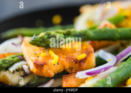 Salad with fried halloumi, asparagus and orange zest. Close up. Dark concrete background - Stock Photo