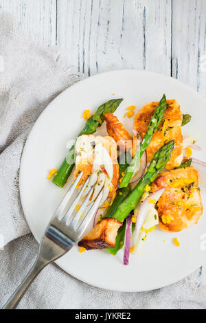 Salad with fried halloumi, asparagus and orange zest. Top view with fork. White wooden background - Stock Photo