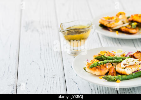 Salad with fried halloumi, asparagus and orange zest. Copy space. White wooden background - Stock Photo