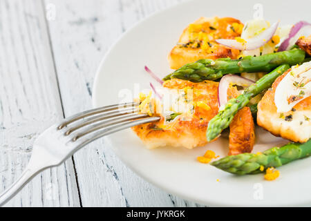 Salad with fried halloumi, asparagus and orange zest. Close up. White wooden background - Stock Photo