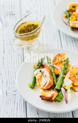 Salad with fried halloumi, asparagus and orange zest. White wooden background - Stock Photo