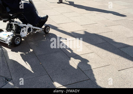 Man with just legs riding a mobility scooter on a tiled grey pavement with long strong shadows - Stock Photo
